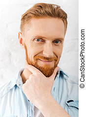 Bearded handsome. Portrait of bearded man holding hand on chin and looking at camera while standing against brick wall