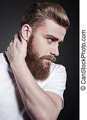Bearded handsome. Portrait of thoughtful young bearded man touching his neck and looking away while standing against grey background