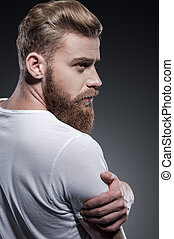 Bearded handsome. Rear view of thoughtful young bearded man looking over shoulder while standing against grey background
