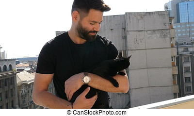 Bearded hipster guy holding a big beautiful black cat in...