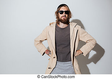 Bearded hipster man wearing sunglasses standing isolated