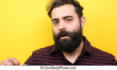 Bearded hipster man winks silly to the camera in slow motion...