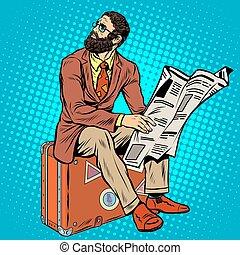Bearded hipster traveler reading a newspaper