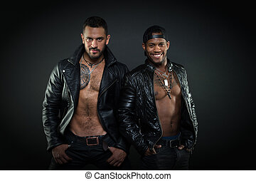 Bearded Hispanic man with six pack and hairy chest, masculinity concept. African man with cheerful broad smile. Models in dark leather jackets on bare torsos. Brutal macho with tattoos