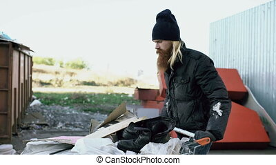 Bearded homeless man walking down the street with shooping...