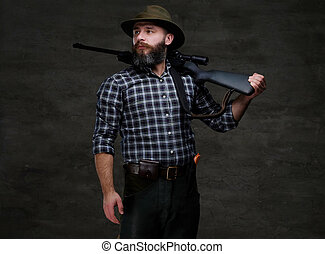 Bearded hunter in a fleece shirt and hat holds on his shoulder a rifle with sight, looking away.