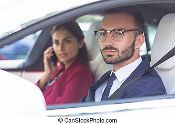 Bearded husband driving car while wife speaking by phone