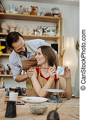Bearded husband hugging his wife working in workroom