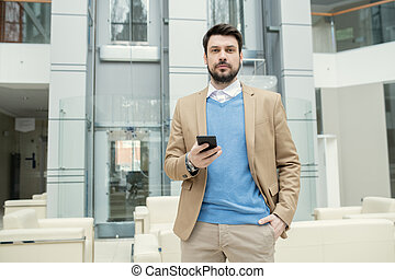 Bearded lawyer checking smartphone in lobby