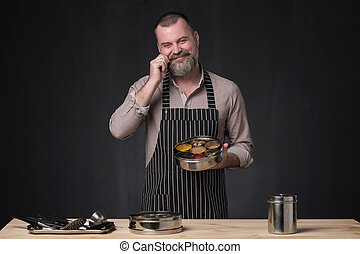 Bearded male chef showing different spices he uses.