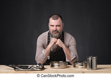 Bearded male chef showing different spices he uses. Secret of delicious food.