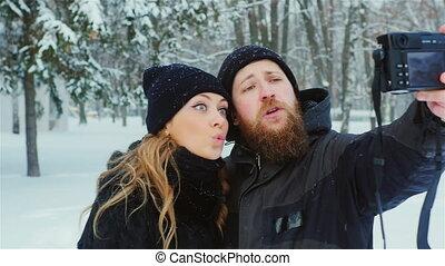 Bearded man and a beautiful woman making selfie