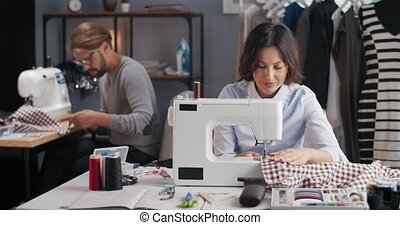 Concentrated bearded man and beautiful woman tailoring fashion clothing on sewing machine. Mature couple working together at small own atelier.