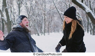 Bearded man and woman having fun in the winter forest