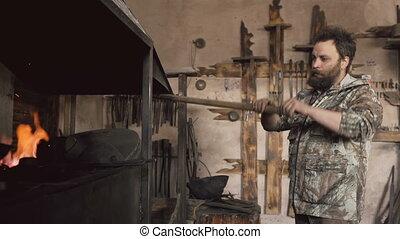 Bearded man blacksmith burning original forge fireplace with...