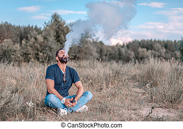 Bearded man blows up a couple an electronic smoke device on the grass. Vaping.