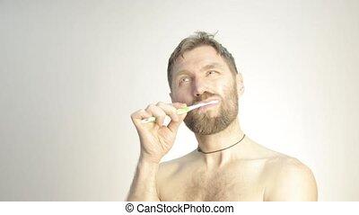 bearded man brushing his teeth in bathroom.
