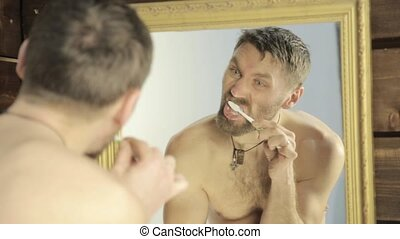 bearded man brushing his teeth in front of mirror in bathroom