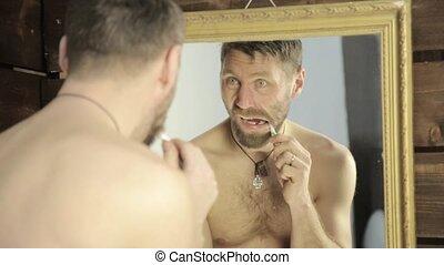 bearded man brushing his teeth in front of mirror in bathroom