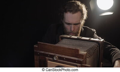 Bearded man carefully restores old retro photo equipment, adjusts lens, looks at wooden camera with smile enjoys repair spreading hands in pleasure. Repair antique obsolete camera in isolated room.