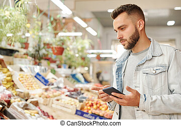 Bearded man checking groceries list