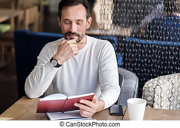 Bearded man checking his notes
