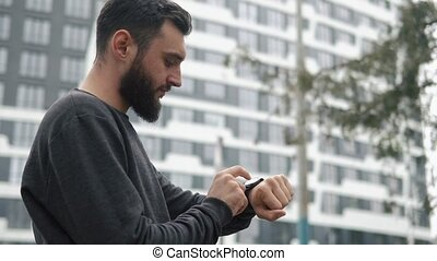 Bearded man checks his smart watch standing somewhere in the city