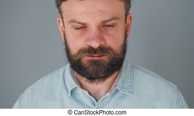 Bearded man chewing bubble gum. Man blowing out a bubble of chewing gum. Bad habit concept