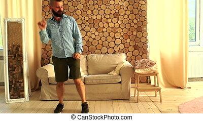 Bearded man dancing inside house. Happiness or good mood...