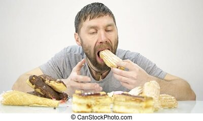 bearded man devours a cake. harmful but delicious food.