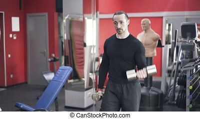 Bearded man doing alternate dumbbell lifts in a gym