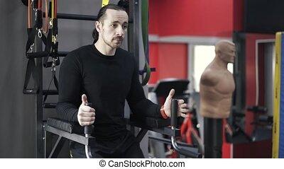 Bearded man doing leg raises in a gym