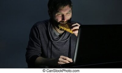 bearded man eating sandwich in front of a laptop.