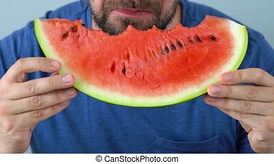 Bearded man eats a juicy watermelon. Close-up