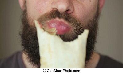 Bearded man eats kebab - street food
