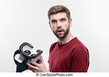 Bearded man feeling excited holding virtual reality glasses for the first time