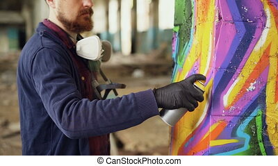 Bearded man graffiti painter is using aerosol paint to...