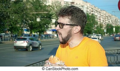 Bearded man greedily eating fresh tasty hamburger outdoors...