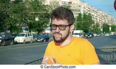 Bearded man greedily eating stale tasteless hamburger...