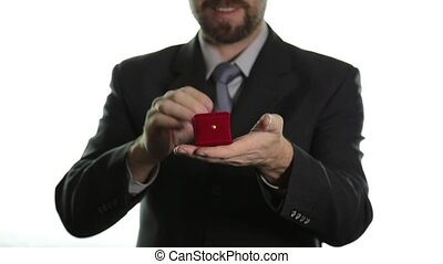 bearded man in a business suit gives a ring in the red box and expresses different emotions
