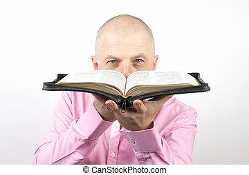 bearded man in a pink shirt looks through an open Bible