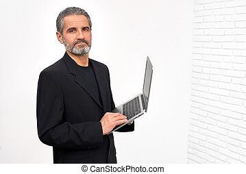 Bearded man in black outfit holding laptop.