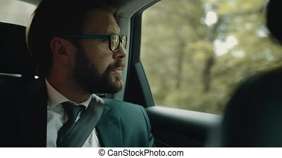 Bearded man in black suit king through window of moving car...