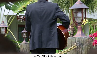 bearded man in black suit plays guitar actively and goes out...