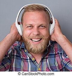 Bearded man in earphones - Portrait of bearded man in white...