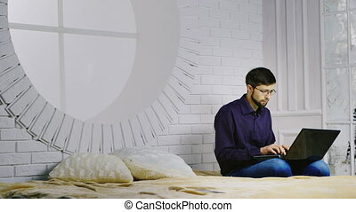 Bearded man in glasses sitting on the bed, uses a laptop