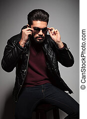 bearded man in leather jacket is putting on his sunglasses