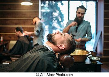 Bearded man in salon cape, barber on background - Bearded...