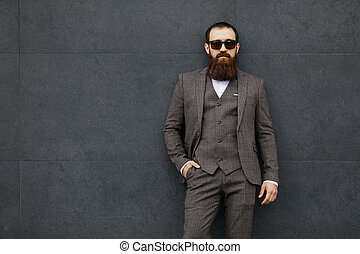 bearded man with a very interesting look with cityscape in the background