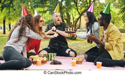 Bearded man is celebrating birthday with friends in park blowing candles on cake shouting and expressing positive emotions while friends are laughing and clapping hands.